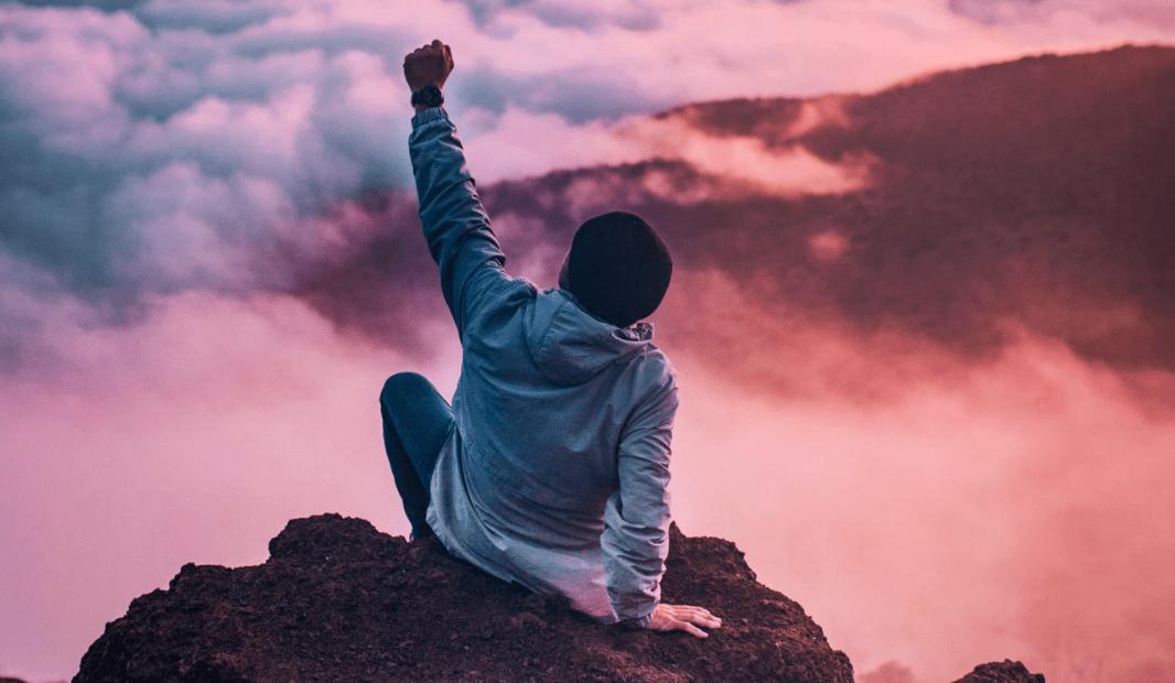 persona feliz del éxito al llegar a la cima de una montaña